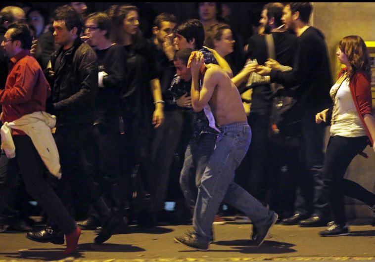 פצוע מחזיק את ראשו מחוץ לאולם בטקלן, בו התרחש הטבח. צילום: רויטרס